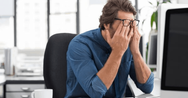 man wiping eyes under glasses stress