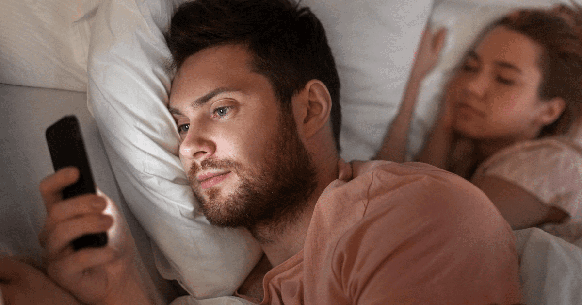 guy messaging fling on phone in bed