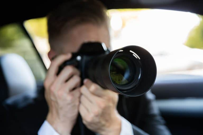 Private investigator conducting surveillance with camera