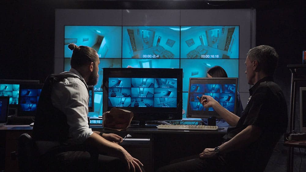 Surveillance team in a modern office with large live screens