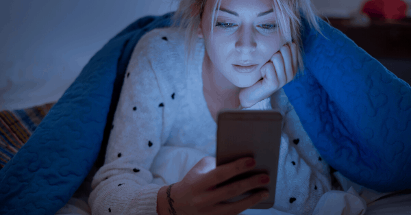 woman looking at phone in bed